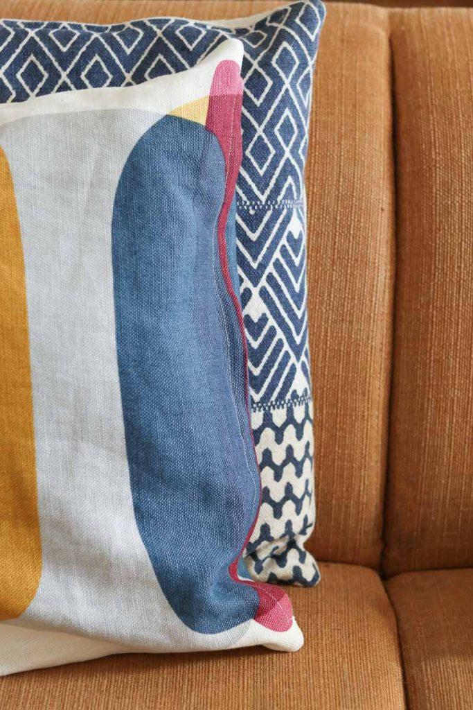 patronen op blauwe kussens op oker gele bank