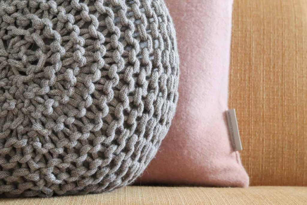 Rond gehaakt kussen grijs en roze kussen wol op oker gele bank