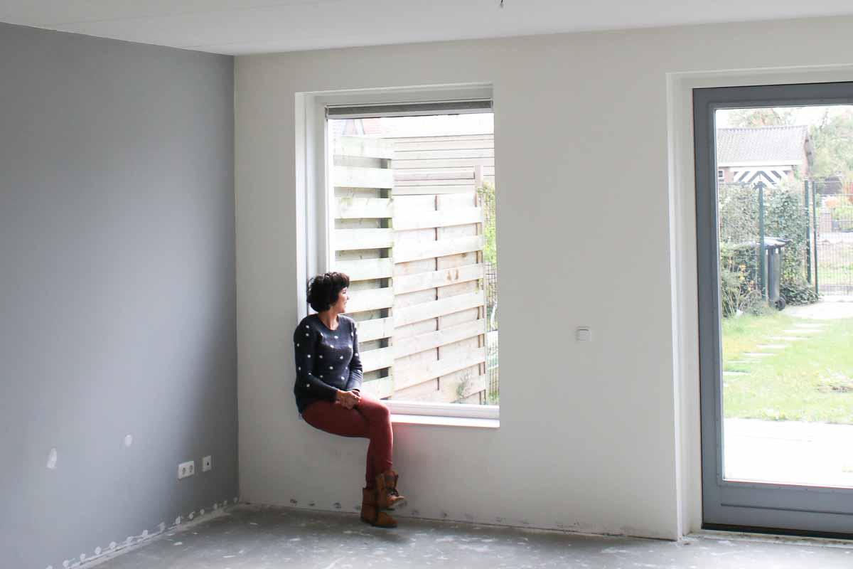 vrouw in raam nieuwbouwhuis