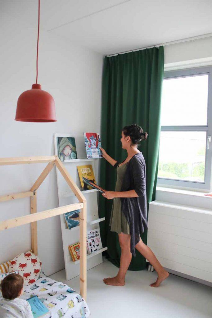 Vrouw zet prentenboeken in DIY boekenkast kinderkamer