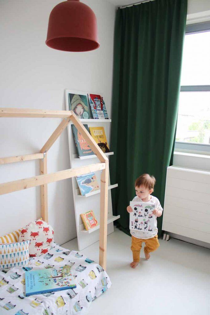 Boekenkast bedhuis kinderkamer dreumes loopt met boek