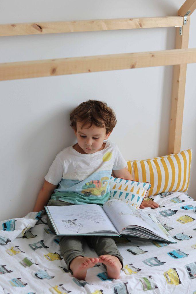 Peuter lees boek in bedhuis