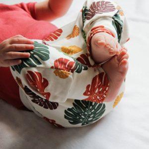 Lachende baby met bladeren broekje in kleur aan